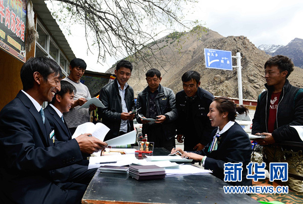 """2014年5月7日,西藏自治區加查縣農業銀行工作人員在農牧民家門口辦理""""四卡""""金融產品。新華社記者 普布扎西 攝.jpg"""