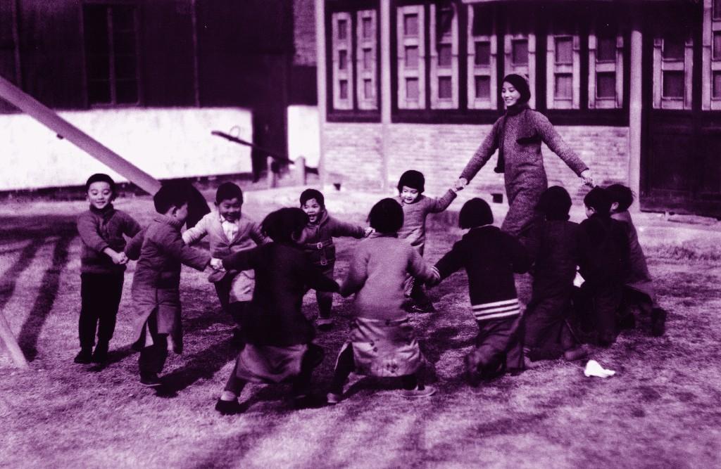 5.1935年12月30日,南京金陵女子文理学院的一位年轻的幼教老师带着孩子们在草坪上做游戏。秦风供图。(原载《老照片》第6辑).jpg