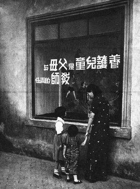 7.1936年,江苏镇江民众教育馆的宣传橱窗前,一位母亲正在给两个女童讲解。吴寅伯摄。(原载《老照片》第12辑).jpg